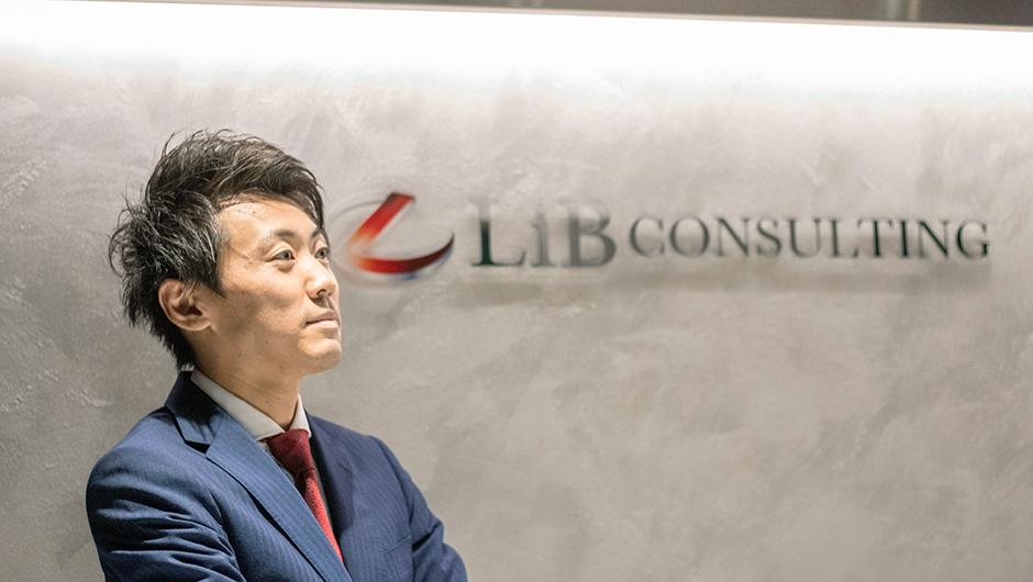 リブ・コンサルティングのコンサルタント鈴木智大さんがロゴの前に立った画像