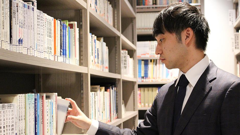 グロービス尾花宏之さんの本を手に取る画像
