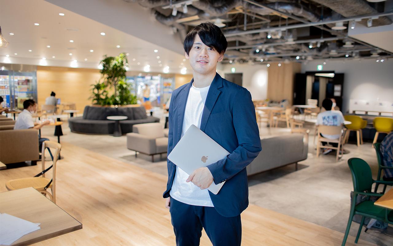 サイバーエージェント稲富龍太郎さんがMacbookを持って立つ姿